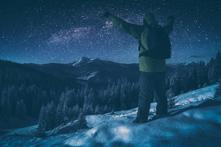 Hiker standing with raised hands against starry night sky with milky way above the winter mountain valley.