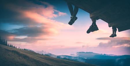 Hikers sit on a wooden flooring above the carpathian mountain valley and enjoy colorful clouds in a light of sunset. Instagram stylisation.