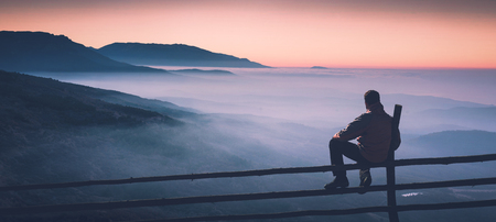 Man sitting on a wooden fence and enjoy mountain valley covered with blue fog. Instagram stylization.