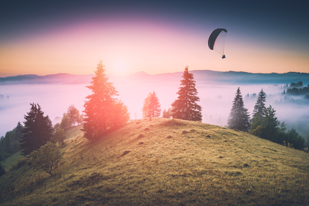 Paragliding silhouette in a light of sunrise above the misty valley. 版權商用圖片 - 78844959