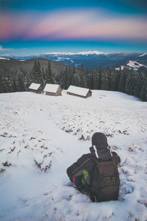 Hiker sits on a snow in a mountain valley and contemplates the winter landscape. Instagram stylization.