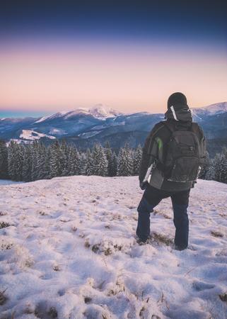 등산객대로 산 계곡에서 snow-capper 언덕에 서 서 겨울 풍경을 contemplates. 스톡 콘텐츠