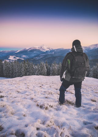 Hiker standing on a snow-capper hill in a Carpathian mountain valley and contemplates the winter landscape. Banco de Imagens