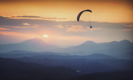 Paraglide silhouette in a light of sunrise above the misty valley. Instagram stylization. Stock Photo