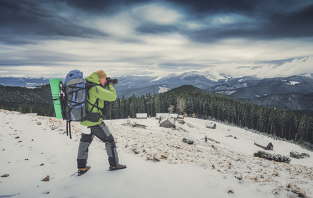 Photographer with a camera, taking photos of beautiful winter mountain valley with dramatic clouds in a sky. Instagram stylization.