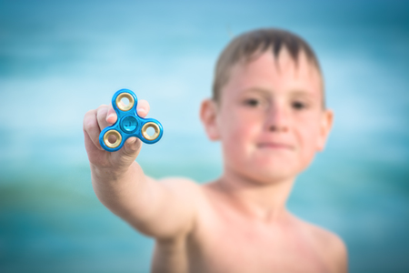 Young boy shows fidget spinner stress relieving toy.