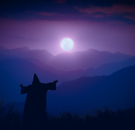 Silhouette of fairy wizard standing on a mountain hill and welcome rising of the full moon. Night landscape.