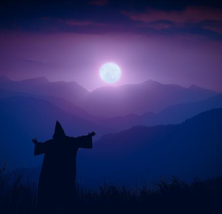 sotana: Silueta del mago de hadas que se coloca en una colina de la montaña y una recepción agradable de la Luna Llena. Paisaje nocturno.