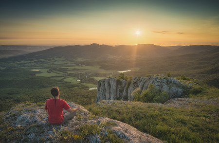 Tourist sitting on a rocky hill and enjoy majestic sunset above Crimea mountain valley. Stock Photo