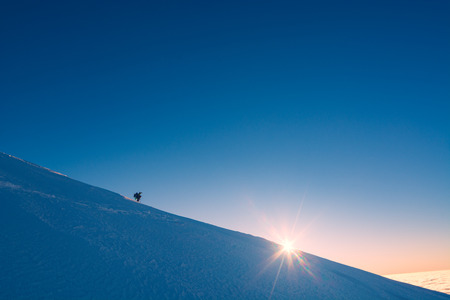 A climber standing on a snowy slope and looking to the sun. Sunset sky on a horison.