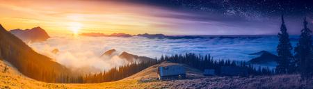 Bijeenkomst van de dag en de nacht in een mistige bergvallei met oude houten huizen op een heuvel.