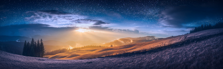 The meeting of day and night in a mountain valley with wonderful gold light on a hills and bright stars in a sky.