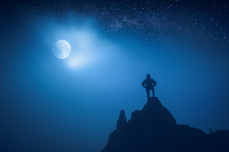 Silhouette of man standing on a cliffs edge against night moon in a starry sky. Stock Photo
