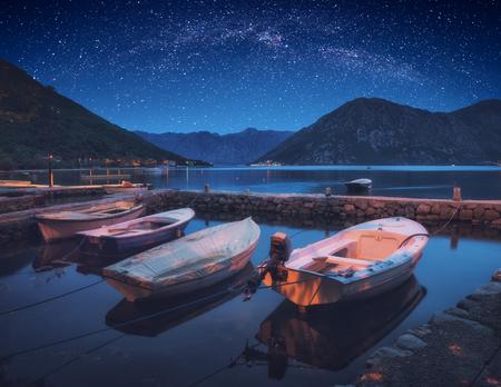 Boats in a Boka-Kotor bay under the night starry sky. Adriatic sea, Montenegro, Europe. Stock Photo