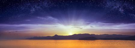 Het spijzen van dag en nacht boven de zee en de bergen van de Krim. De zonsopgang met sterrenhemel. Fantastisch landschap. Stockfoto