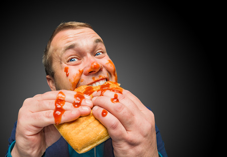Funny hungry fat man dirty by ketchup eating the tasty sandwich.