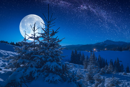 Majestic full moon rising above the carpathian mountain valley with small village on a hill covered with fresh snow. Fantastic milky way in a starry sky. Christmas winter night. Stock Photo