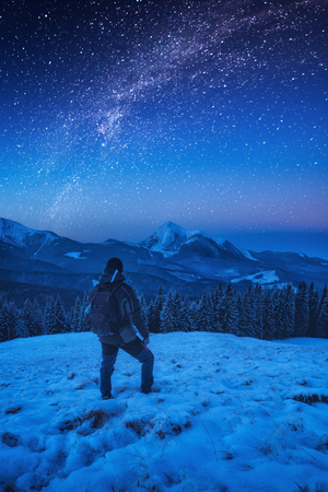 A hiker man with backpack standing on a snowy slope at night. Milky way in a starry sky above the mountain top.