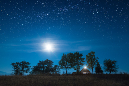 Full moon rising above the mountain village with wooden house on a hill. Many stars in a sky. Stock Photo