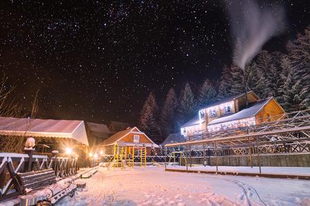 Ukrainian carpathian village covered with snow. Yard illuminated by christmas lights. Many stars in a night sky.