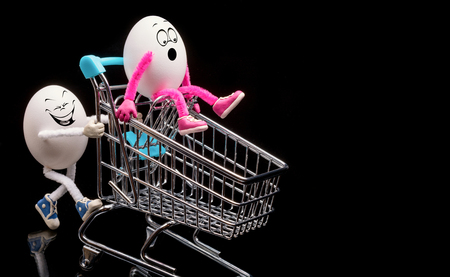 Two funny eggs ride a cart from a supermarket. Stock Photo