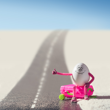 Funny egg girl hitchhiking on a road in a desert. Travel concept. Stock Photo