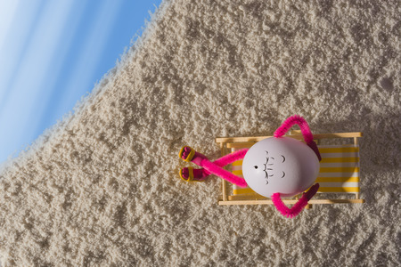 Happy egg lying on a deck chair near the sea. Vacation and travel concept. Stock Photo