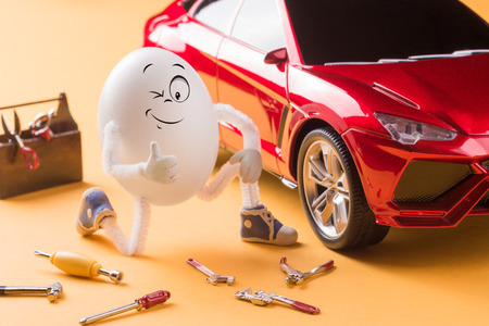 Funny egg mechanic repair the car. Stock Photo