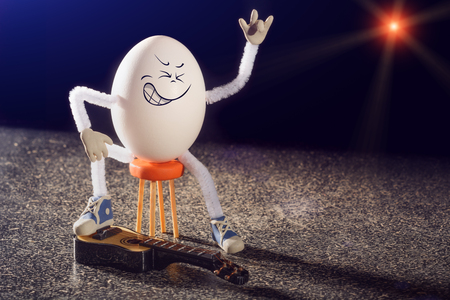 Funny egg rocker guitarist sitting on a chair with guitar on a stage. Stock Photo
