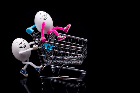 Two funny eggs ride a cart from a supermarket. Preparing for Easter. Stock Photo