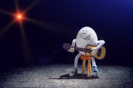 Funny egg rocker guitarist sitting on a chair with acoustic guitar on a stage.