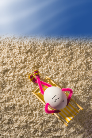Happy egg lying on a chaise longue at sandy beach and enjoy the sea. Vacation and travel concept.