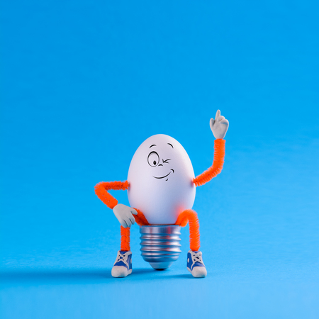 Winking Easter egg toy in the shape of a light bulb on a blue background. Innovation business concept idea.
