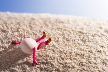 Easter egg lying on a sandy beach and enjoy the sea. Vacation and travel concept.