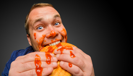 Funny hungry fat man dirty by ketchup bites the tasty panini sandwich. Stock Photo