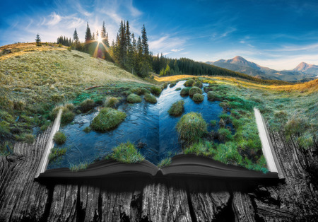 Alpine mountain valley in a light of sunrise on the pages of an open magical book. Majestic landscape. Nature concept.