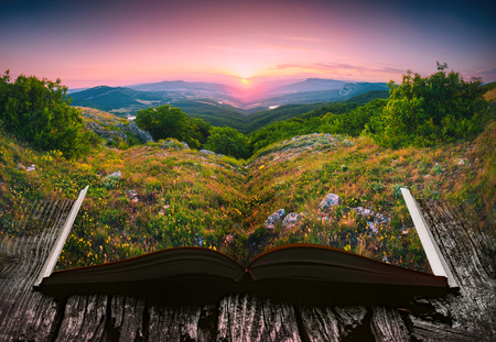 Sunset in a mountain valley on the pages of an open magical book. Majestic landscape. Nature and education concept.