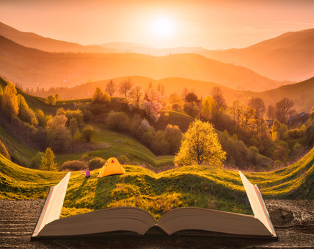 Girl hiker near the camping tent on a hill in a mountain valley on the pages of an open magical book. Majestic landscape. Nature and education concept. Stock Photo