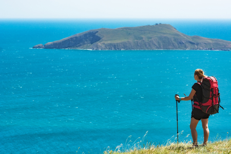 Young woman hiker with backpack and trekking sticks standing on a hill and looking to the cape in a sea. Travel and adventure. Stock Photo