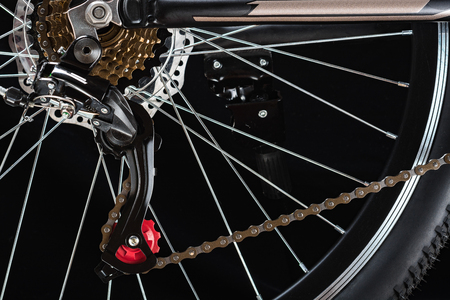 Mountain bicycle photography in studio. Bike wheel with disc brakes and chain. Bike part.