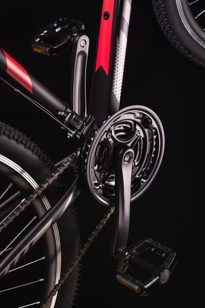 Mountain bicycle photography in studio. Bike pedals with chain and wheel. Bike part.