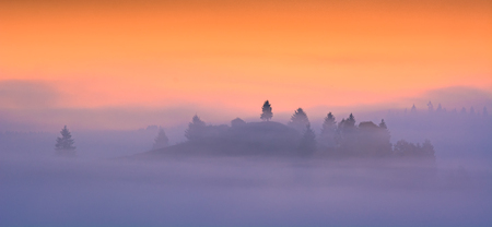 Majestic colorful morning in a valley covered with blue fog. 版權商用圖片