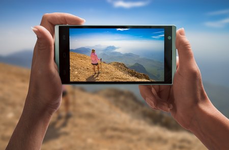 Girl hiker in a mountain valley on a screen of smartphone taking by girl hand. Travel concept.