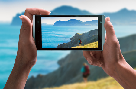 Girl hiker near the sea on a screen of smartphone taking by girl hand. Travel concept.