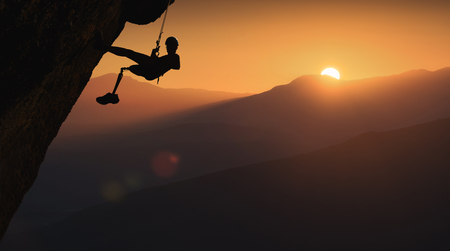 Silhouette of climber with prothesis on a cliff in a light of sunrise. Active people with disabilities.