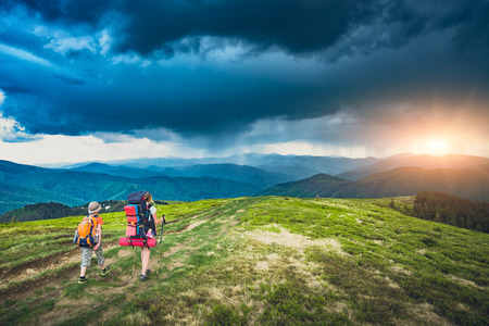 Mother with son and baby in a carrying for child on a road in a mountain valley with rainy dark clouds in a sky. Travel and family concept. 版權商用圖片