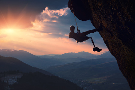 The climber with prothesis on a cliff in a mountain valley at sunset. Active people with disabilities. 版權商用圖片