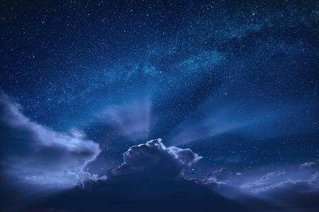 Beautiful moon beams in a night starry sky over dramatic clouds. 版權商用圖片