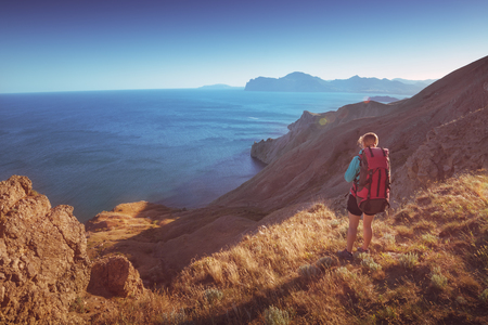 Girl hiker on a cliff above the sea at sunset time.
