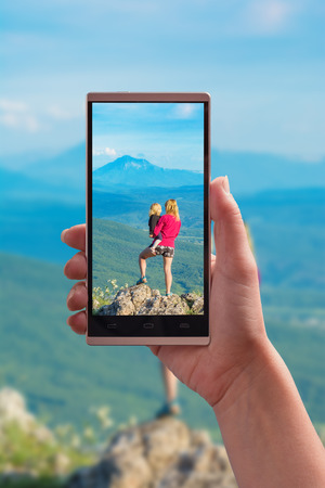 Mother with child on a cliff in a mountains on smartphone screen. Travel concept. 版權商用圖片